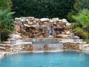 Beautiful water feature / waterfall for a swimming pool that spills into a hot tub